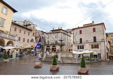 ASSISI ITALY 30 JUNE 2017: Medieval square with old water fountain and historical buildings Assisi Umbria Italy