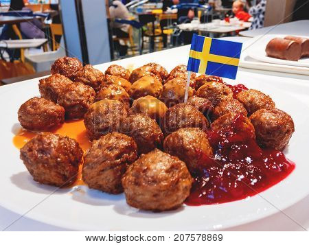Fresh tasty meatballs with cranberry sauce on white plate with Swedish flag.
