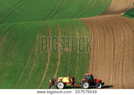 Modern Red Tractor Plowing And Spraying On Field. Small Tractor Working On A Colorful Spring Field.Agriculture Tractor Creating Abstract Brown Background Texture.Rural Scenic Landscape.Czech Republic