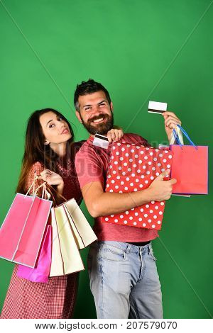 Guy with beard and girl with happy faces do shopping. Man with beard holds credit card and polka dotted box. Shopping and free time concept. Couple in love holds shopping bags on green background.