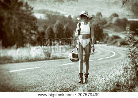 Slim girl with sunhat and glasses walking on road with travel bag