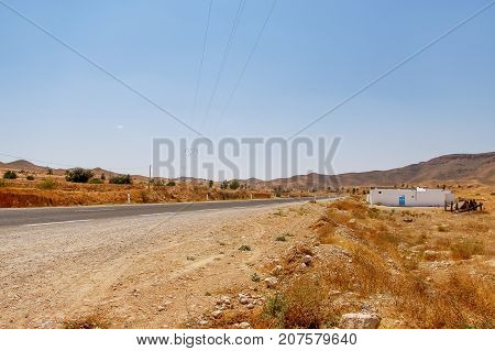 Road somewhere in Tunisia through Sahara desert. Africa landscape with power lines and asphalt road.
