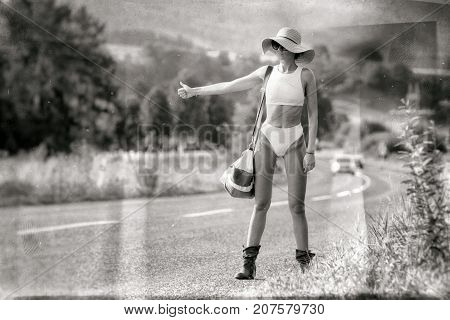 Hitchhiking young woman in bikini and sunhat on stopping the car