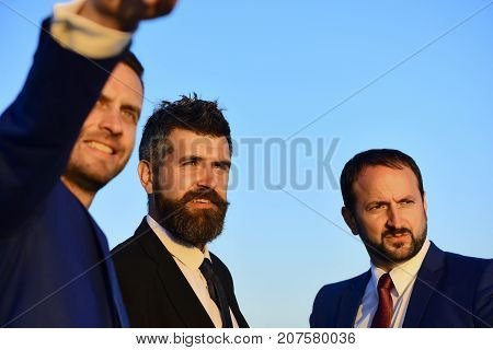 Businessmen with smiling faces in formal suits and ties on blue sky background. Business confidence and teamwork concept. Company leaders show worksite and new goals. Executives take a walk outside