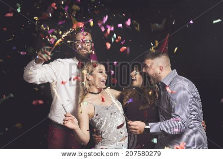 Two beautiful young couples having fun at New Year's party wearing party hats holding firework sprinkles and dancing