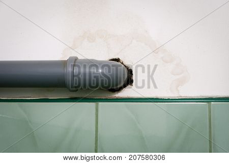 Wet stain on white wall around polypropylene gray pipe of water installation.