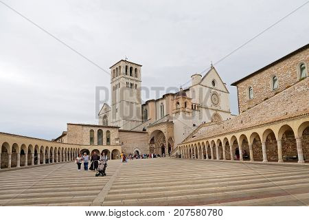 ASSISI ITALY 30 JUNE 2017: Famous Basilica of St. Francis of Assisi (Basilica Papale di San Francesco) with Lower Plaza at sunset in Assisi Umbria Italy