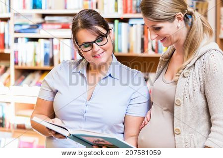 Two friends reading book in bookstore together in front of shelf