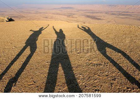 Three shadows of tourists in Negev desert Israel.