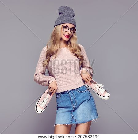 Young Woman Having Fun Surprised Smiling. Fashion. Shopping Sales Discount concept. Pretty Blond in Stylish fashion Autumn Winter Outfit with Sneakers.Playful Hipster Model Girl in Cozy Jumper, Glasses