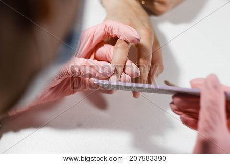 Woman getting nail manicure in salon. Care for hands. manicure master makes the nails smooth using the nail file with smooth ends purple.