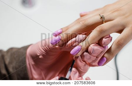 the master in the salon makes a manicure Nail polish coating. A big plan. Beautiful hands