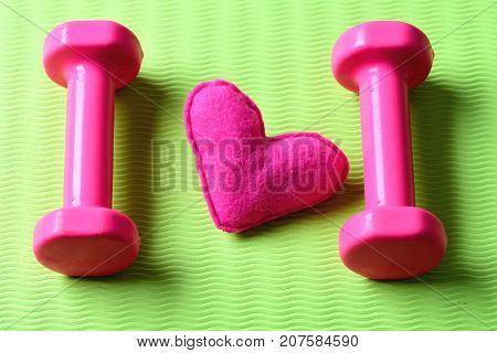 Heart Decoration Near Barbells On Yoga Mat. Female Style Workout