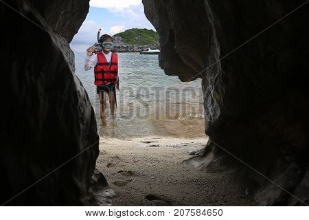 Asian girls are snorkelling on the beach in front of the cave.