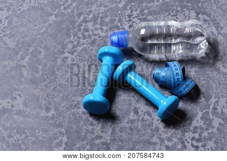 Dumbbells In Cyan Color, Water Bottle And Measuring Tape