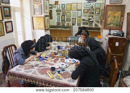 ISFAHAN, IRAN - JUNE 25, 2007: Unidentified muslim women artists in black headscarfs paint traditional Persian miniature in a workshop in Isfahan, Iran.
