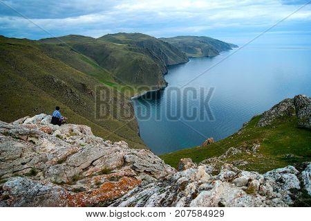 Girl lost in landscape in lake Baikal, Aya bay.