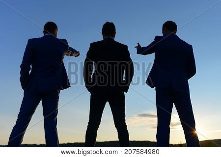 Silhouettes Of Company Leaders Standing On Sunset Sky Background.