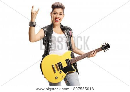 Joyful punk girl with an electric guitar making a rock hand gesture isolated on white background