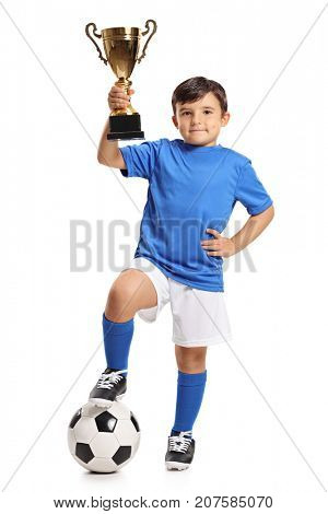 Full length portrait of a small boy in a blue jersey with a football and a gold trophy isolated on white background