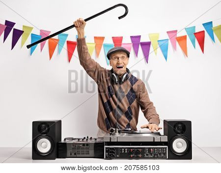 Overjoyed senior with a cane playing music on a turntable against a wall with decoration flags