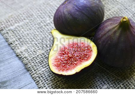 Fresh ripe fig fruits on a burlap cloth background.Whole and sliced figs.Ficus carica fruit. Selective focus.
