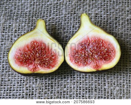 Fresh ripe fig fruits on a burlap cloth background.Sliced organic figs.Ficus carica fruit. Selective focus.