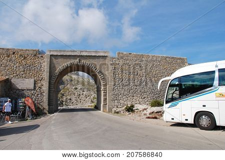 MAJORCA, SPAIN - SEPTEMBER 6, 2017: A tourist coach stops at a cafe by a viaduct on the twisting road to Sa Calobra high up in the Tramuntana mountains on the Spanish island of Majorca.