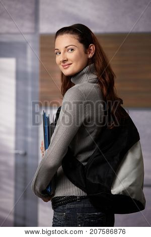 Happy female student standing on school corridor, holding workbooks, looking back over shoulder, smiling.