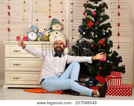 Celebration and New Year mood concept. Santa Claus in white hat with happy face. Man with beard holds champagne glass. Guy sits near Christmas tree and bureau with toys on wooden wall background