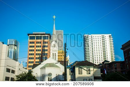 Religious Cross on high Steeple on top of Church Blue Sky background Christian Religion in Downtown Houston , Texas , USA