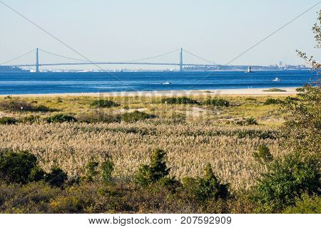 A scenic look at the Verrazano Narrows Bridge from across the Sandy Hook and Lower Bay.