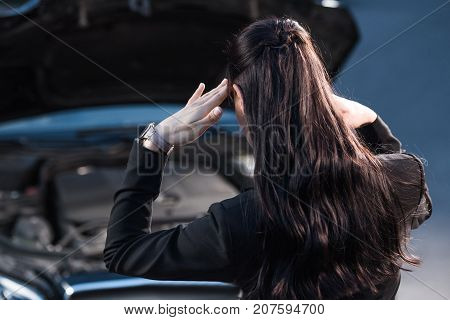 Troubled Woman Looking At Car Engine