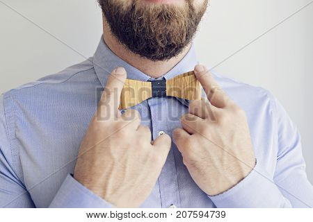 Close up Portrait Bearded Man in a Blue Shirt Adjusts wooden Bow Tie with hands, selective focus Happy Boss's Day Concept