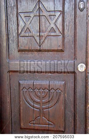 A door made of wood in the israeli city of safed shows the Jewish symbols the menorah and the star of david