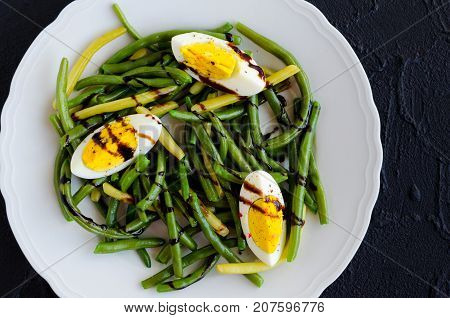 Fresh summer warm salad with cooked green beans with boiled eggs and sauce balsamico glassa in white plate on black stone background. Healthy eating. Vegetarian food concept. Top view.
