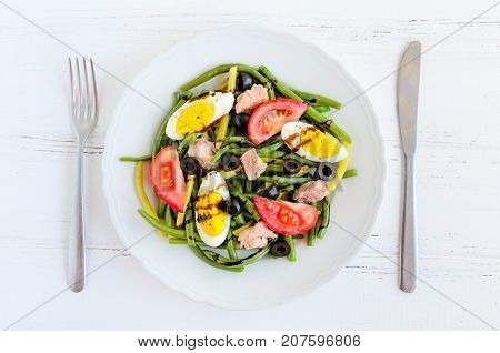 Summer warm salad with cooked green beans tuna tomatoes boiled eggs and sauce balsamico glassa in white plate with knife and fork on wooden background. Healthy eating concept. Top view.