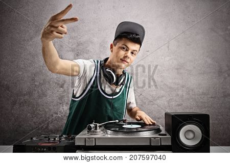 Teenage DJ making a pace sign against a rusty gray wall