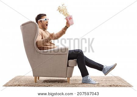 Terrified guy with 3D glasses and popcorn sitting in an armchair isolated on white background