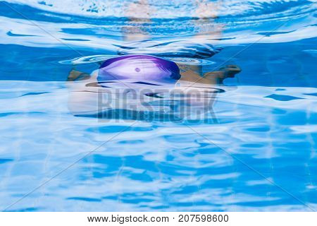 boy swimming under water in a clean and clear swimming pool about to surface - good for excercise or good health concept