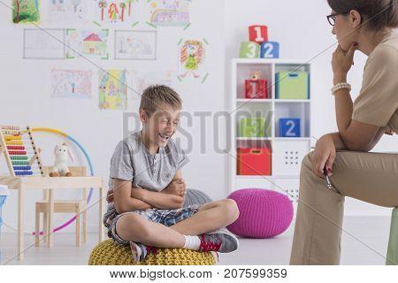 Young Boy Sits On A Yellow Pouf