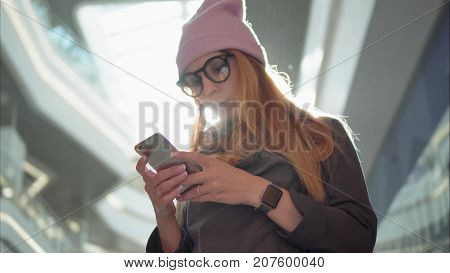 A young hipster female using app on the smartphone in the big mall