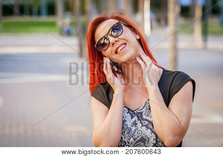 Portrait of a pretty Caucasian girl with sunglasses talking on a cellular phone outside stock image. Dating, flirting, positive, attraction, smile, vitality, energy, full of life, healthy person.