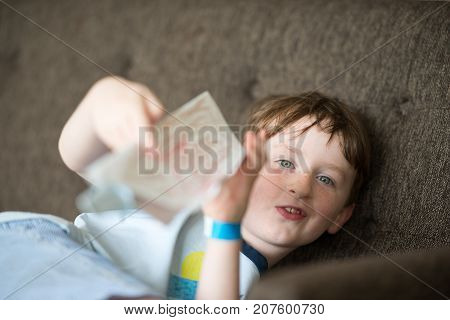 Young boy lying relaxing on a sofa while reading looking up around the paper with a mischievous smile