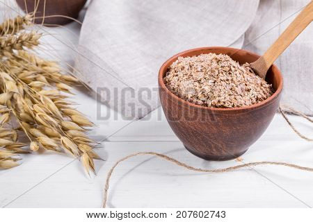 Wheat, Oat bran in clay  bowl and ears of wheat and oat.  Dietary supplement to improve digestion. On white background