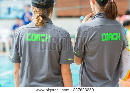 back of two coach's grey shirts with the green word Coach written on them good background for sport or coaching theme