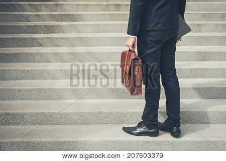 Businessman wearing black suit holding bag and folder standing at first step of the stair