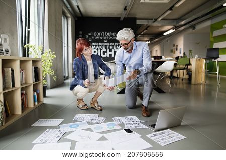 Two business people in the workplace. Woman and man in the office consulting a project together.