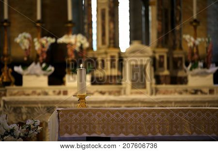 inside a church with the altar and candle lit during Holy Mass