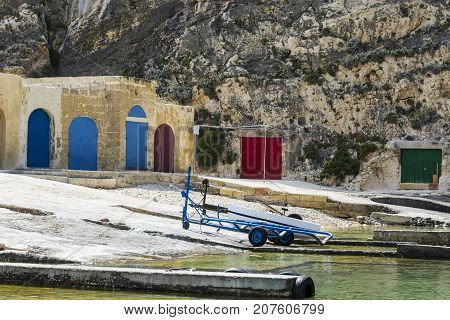 Boat on the trolley for launching on the water near hangars. The Inland Sea is a lagoon of seawater on the island of Gozo linked to the Mediterranean Sea through a narrow natural arch.